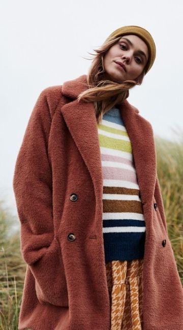 Jeune femme portant un manteau et un pull éthique